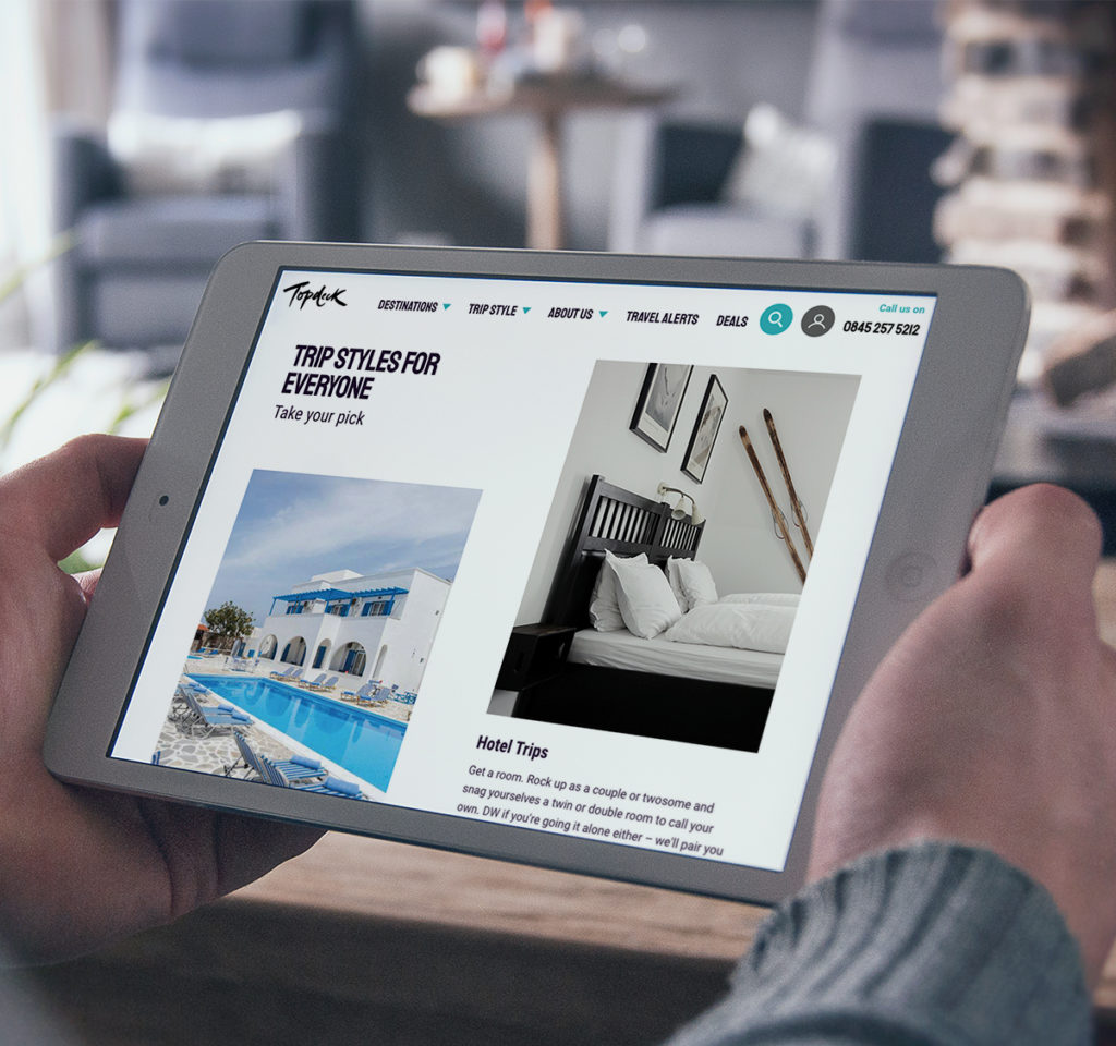 person holding an ipad looking at the topdecj website